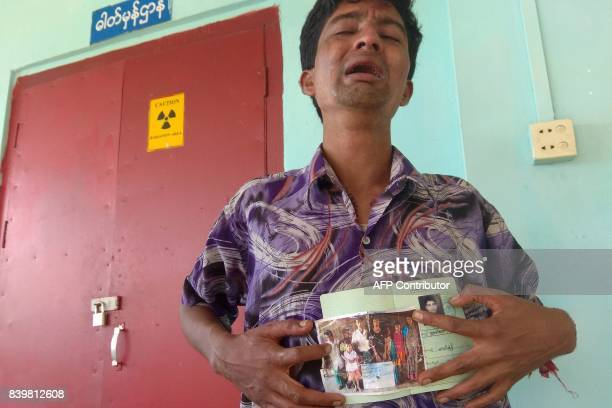 A man shows a picture of members of his family whom he says were killed by Rohingya militants at Maungdaw hospital on August 27 2017 The victims who...