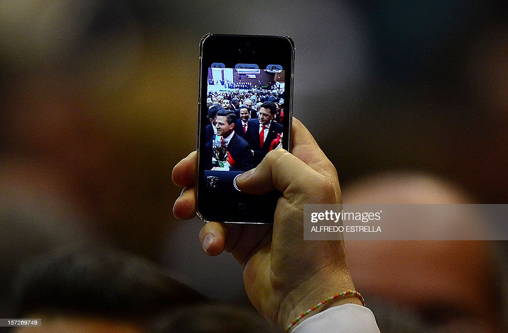 A man shows a picture on his phone of incoming Mexican President Enrique Pena Nieto as he arrives for his inauguration ceremony at the Congress in Mexico City on December 1, 2012. Pena Nieto was sworn in as president of Mexico on Saturday following protests by leftist lawmakers inside the congress and clashes between demonstrators and police outside. AFP PHOTO/Alfredo Estrella