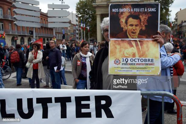 A man shows a poster of French President Emmanuel Macon depicted as a devil near a banner reading 'Fight' Nearly 3000 protesters took to the streets...