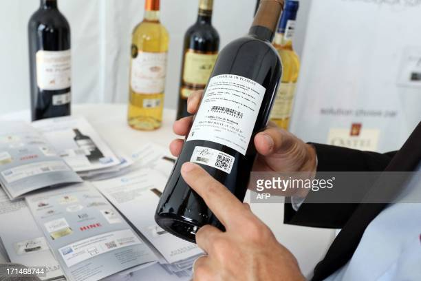 ABADIEA man shows a special sticker on a wine bottle on June 17 2013 during the Vinexpo trade fair With an hologram and a QR code the labels are made...