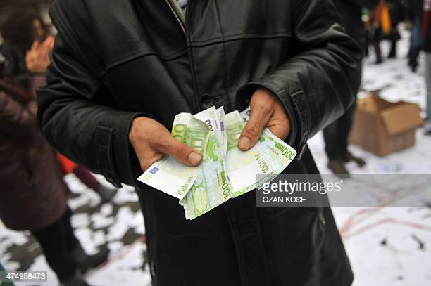 A man shows false 100 euro notes used by demonstrators to illustrate the corruption in the government on February 26 2014 on Istiklal avenue in...