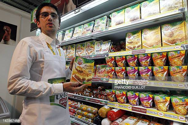 A man shows halal products at a stand of Halal food products on April 3 2012 during the 9th International Halal and oriental products trade fair at...