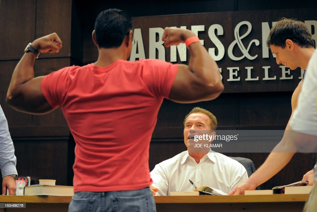 A man shows his bodywork to actor and former California Governor Arnold Schwarzenegger as he signs his memoirs, 'Total Recall - My Unbelievably True Life Story', October 5, 2012 in Los Angeles, California. Schwarzenegger's book, 'Total Recall', named after one of his blockbuster movies, includes details of his marital infidelities, including fathering a child with his housekeeper, leading his wife Maria Shriver to file for divorce.