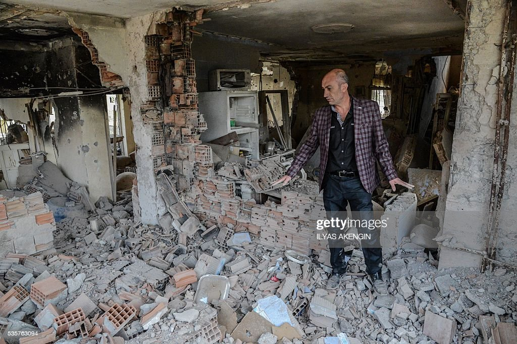 A man shows his destroyed house to journalists following heavy fightings between government troops and Kurdish fighters after the curfew on May 30, 2016 in the majority Kurdish city town of Yuksekova, southeastern Turkey near the border with Iraq and Iran. / AFP / ILYAS