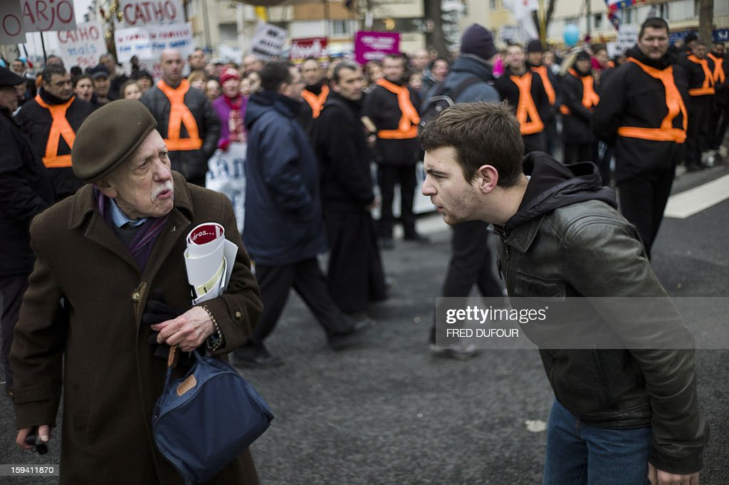 A man (R) shows his disagreement to an old man taking part in a protest against same-sex marriage on January 13, 2013 in Paris. Tens of thousands march in Paris on January 13 to denounce government plans to legalise same-sex marriage and adoption which have angered many Catholics and Muslims, France's two main faiths, as well as the right-wing opposition. The French parliament is to debate the bill -- one of the key electoral pledges of Socialist President -- at the end of this month.
