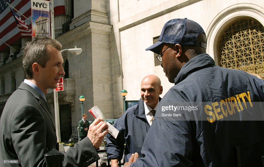 A man shows his identification to a security guard outside the New York Stock Exchange August 6 2004 in New York City. Security at finacial institutions have been hightened after the U.S. Justice Department raised the terror alert.