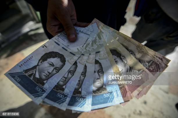 A man shows new 500Bolivarnotes in Caracas on January 16 2017 A new family of currency will progressively come into circulation in the South American...