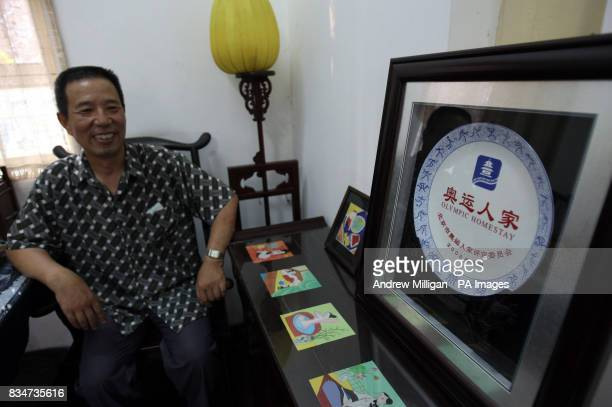A man shows off a plate in his Hutong near Hou Hai lake in Old Beijing China