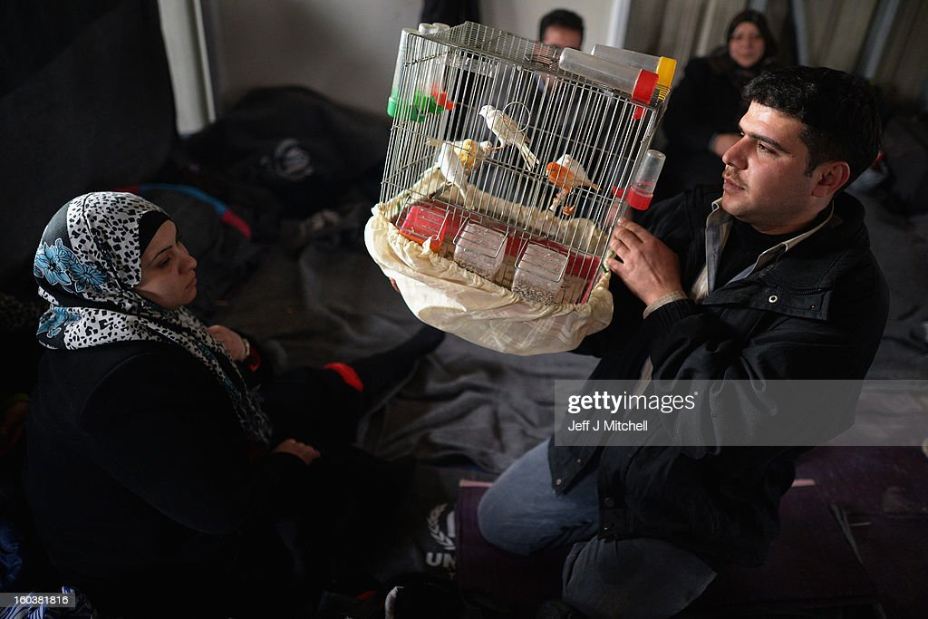 ZA'ATARI JORDAN JANUARY 30 A man shows off his pet birds as new Syrian refugees arrive at the International Organization for Migration at the...