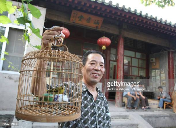 A man shows off some birds as he welcomes people to stay at his home for the Olympic Games near Hou Hai lake in Old Beijing China