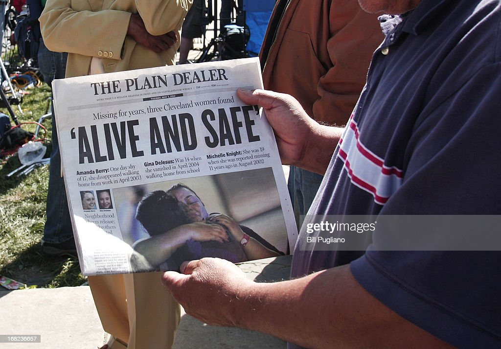 A man shows page one of The Plain Dealer newspaper to a friend while people gather along Seymour Avenue near the house where three women, who disappeared as teens about a decade ago, were found alive, May 7, 2013 in Cleveland, Ohio. Amanda Berry, who went missing in 2003, Gina DeJesus, who went missing in 2004, and Michelle Knight, who went missing in 2002, managed to escape their captors on May 6, 2013. Three suspects, all brothers, were taken into custody.