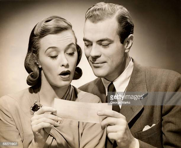 Man shows surprised woman a bank check