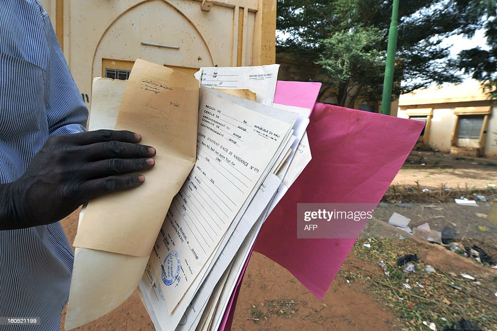 A man shows the birth certificates he picked up, on February 1, 2013, in the Gao town hall looted by former Islamist occupiers. President Francois Hollande visits Mali on February 2, as French-led troops worked to secure the last Islamist stronghold in the north after a lightning offensive against the extremists. Gao's light-skinned Arab and Tuareg residents face the violent anger of their black neighbours since French and Malian troops reclaimed the city from the rebels of the Movement for Oneness and Jihad in West Africa (MUJAO) on January 26.