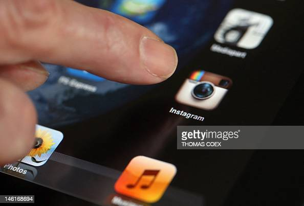 A man shows the smartphone photo sharing application Instagram on an Iphone on April 10 2012 in Paris one day after Facebook announced a...
