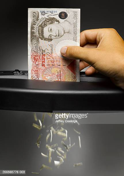 Man shredding fifty Pound banknote
