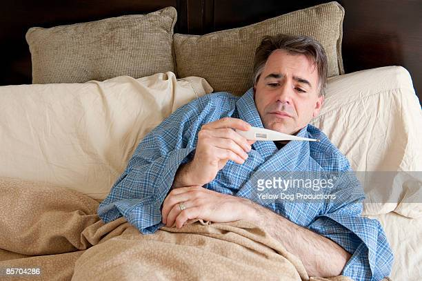 Man Sick in Bed Taking his Temperature