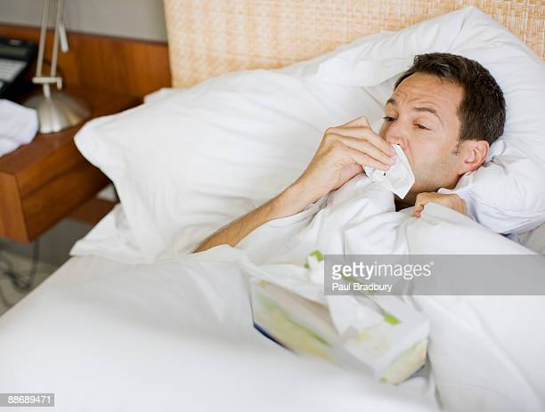 Man sick in bed wiping nose with tissue