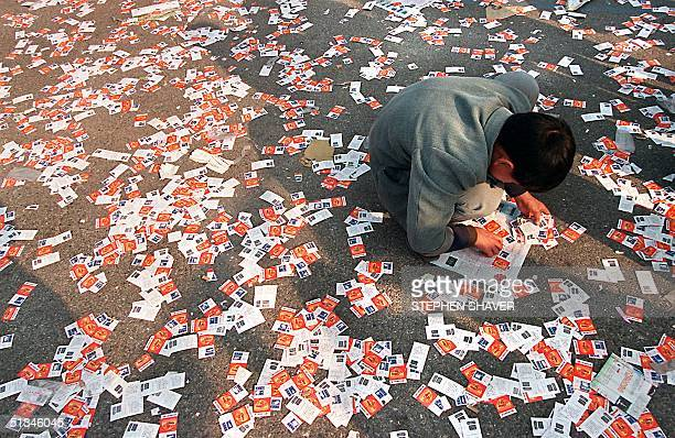 A man sifts through an ocean of scratched tickets hoping to find an 'instant winner' ticket accidentally thrown out 08 November for one of many cars...