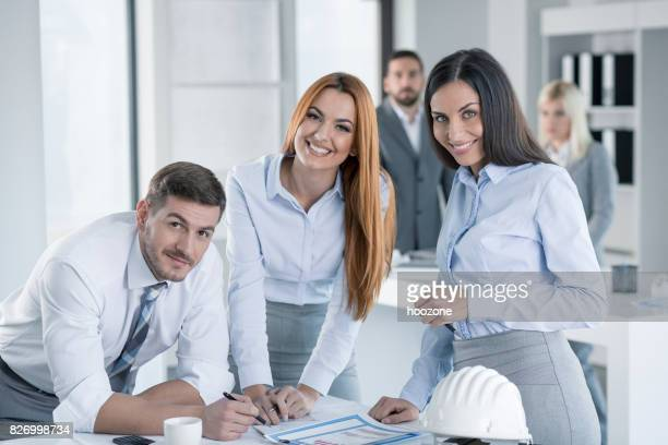 Man signing documents at office guided by two business women