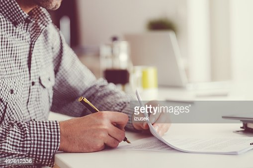 Man signing documents, unrecognizable person