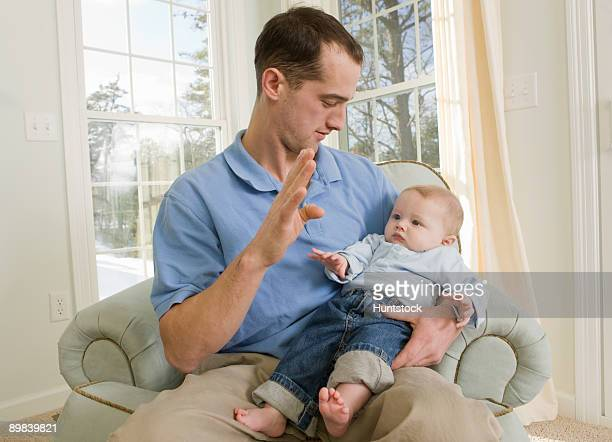 Man signing the word 'B' in American sign language while communicating with his son