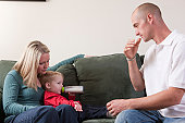 Man signing the word 'Drink' in American Sign Language while his son is drinking milk