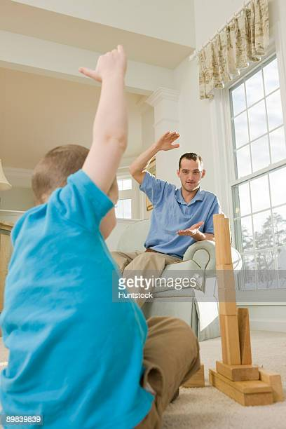 Man signing the word 'Tall' in American sign language while communicating with his son