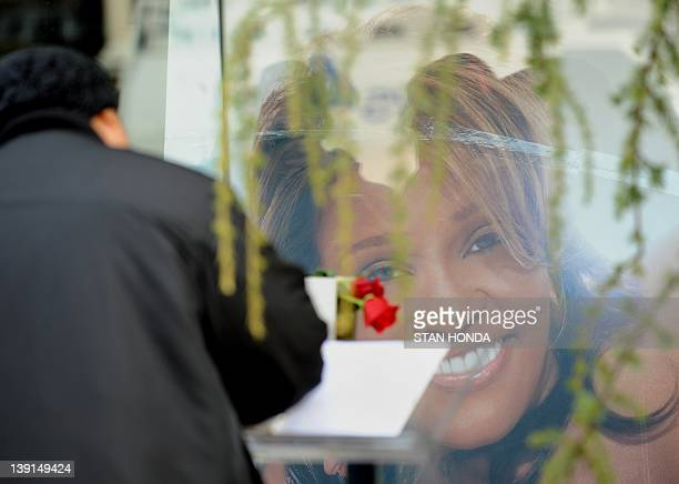 A man signs a condolence book for singer Whitney Houston in front of a large photograph of her outside the Whigham Funeral Home February 17 2012 in...