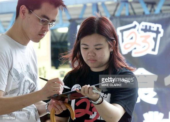 A man signs a petition to protest against the government legislating Article 23 of the Basic Law in Hong Kong 27 June 2003 Despite opposition against...