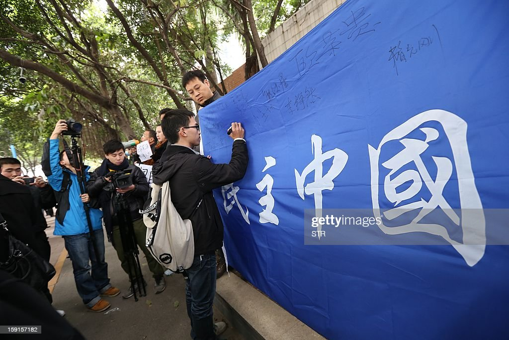 A man signs his name on a giant banner that reads 'Democratic China' outside the headquarters of Nanfang Media Group in Guangzhou on January 9, 2013. A Chinese weekly newspaper at the centre of rare public protests about government censorship will publish as usual on January 10, a senior reporter said, following reports of a deal to end the row. The row at the popular liberal paper, which had an article urging greater rights protection replaced with one praising the ruling communist party, has seen demonstrators mass outside its headquarters in the southern city of Guangzhou.