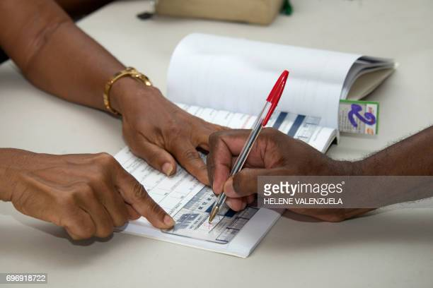 A man signs the register after casting his ballot during the secound round of the French legislative elections at a polling station in PointeaPitre...