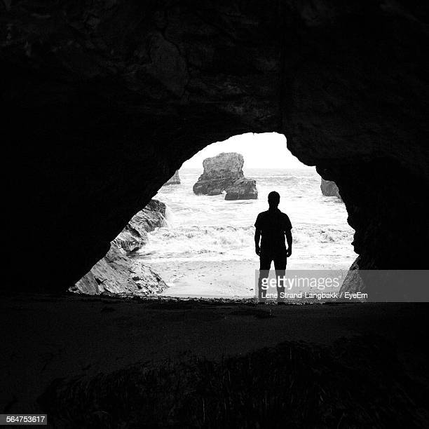 Man Silhouetted Against Arched Cave Facing Sea