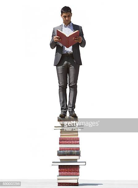 Man sin suit standing on a lot of books reading