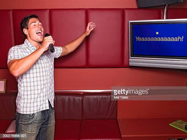 Man singing by screen in karaoke bar, eyes closed