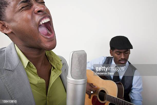 Ein Mann, singen mit einem retro-Mikrofon, Gitarrist im Hintergrund