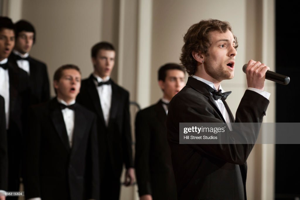 Man singing with choir on stage