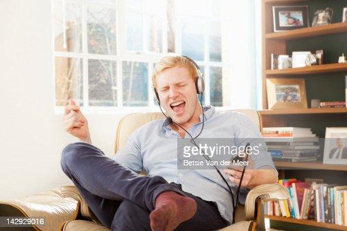 Man singing with headphones on in livingroom. : Stock Photo