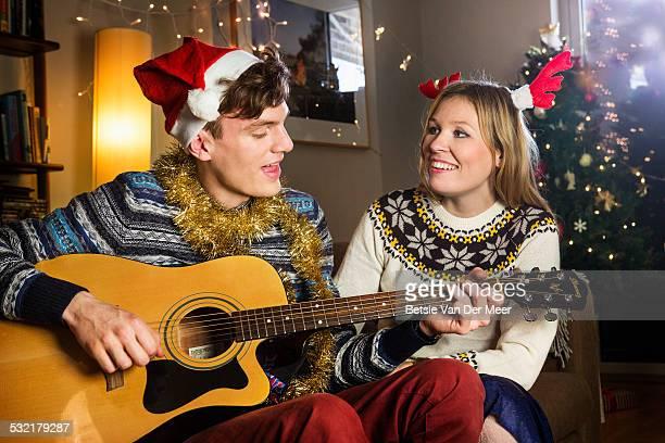 man sings Christmas songs for girlfriend.