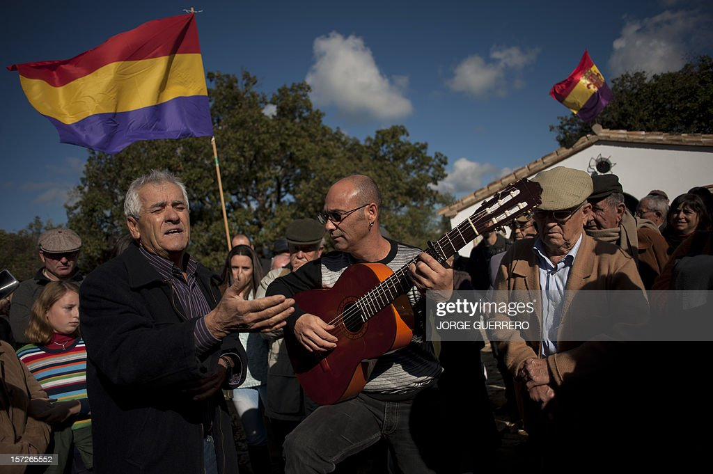 A man sings close to a flag of the Second Spanish Republic during the funeral ceremony for 28 people executed during the Spanish Civil War at La Sauceda Cemetery in Cortes de la Frontera on December 1, 2012. Twenty-eight, seven women and 21 men, of the hundreds of people who were tortured and executed by the forces of Francisco Franco at the 'El Marrufo Estate' in Cadiz during the Spanish Civil war, received a proper burial today, 76 years after their bodies, all shot, were thrown into mass graves.