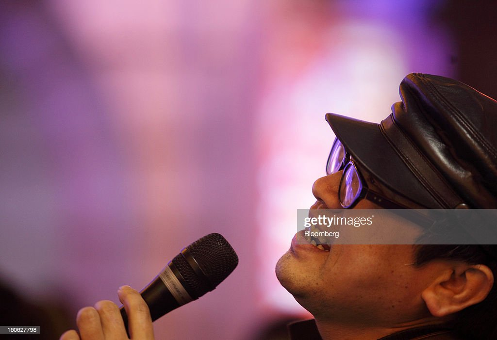 A man sings into a microphone at a karaoke bar at night in the East Nanjing Road shopping area of Shanghai, China, on Friday, Feb. 1, 2013. China's services industries grew at the fastest pace since August as gains in retailing and construction aid government efforts to drive a recovery in the world's second-biggest economy. Photographer: Tomohiro Ohsumi/Bloomberg via Getty Images