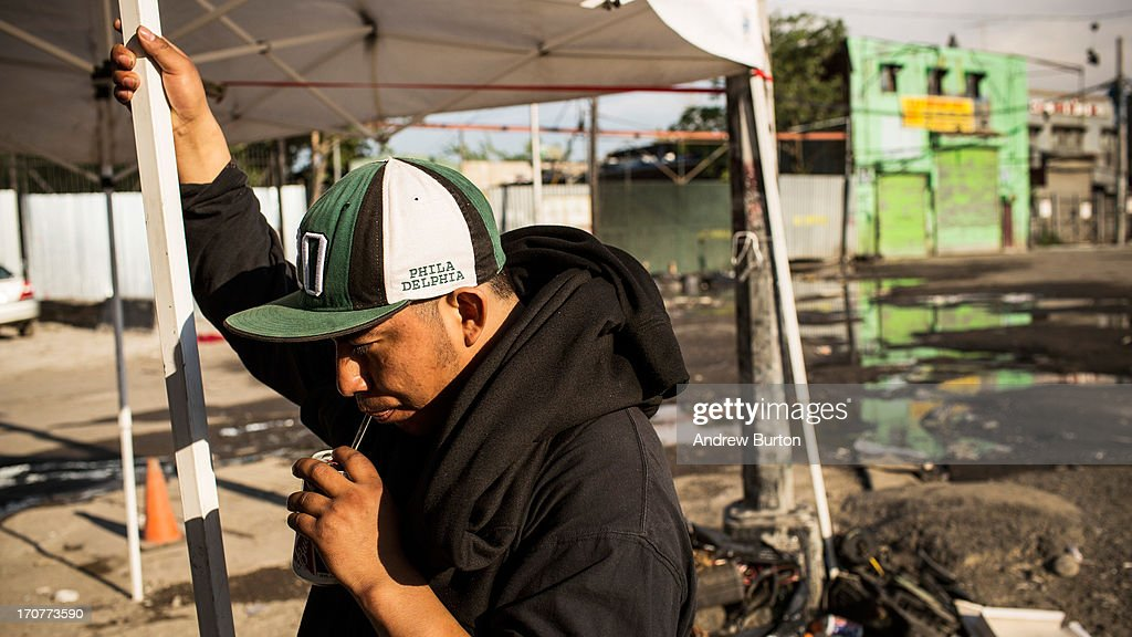 A man sips beer through a straw after a day of work on June 17, 2013 in the Willet's Point neighborhood of the Queens borough of New York City. The Willet's Point Neighborhood, also known as the Iron Triangle, is situated directly next to Citi Field, where the Met's play baseball, and is known for both its car repair shops and lack of paved roads. The future of the neighborhood has been a contentious issue between residents and the city, as the city hopes to further develop the land despite protests from its residents.