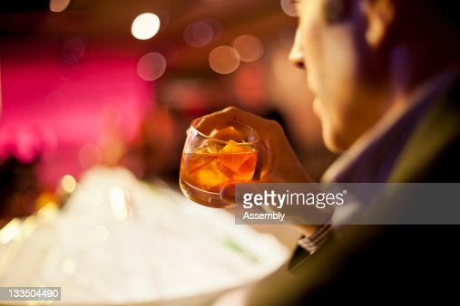 A man sips from his rocks glass at a bar : Stock Photo