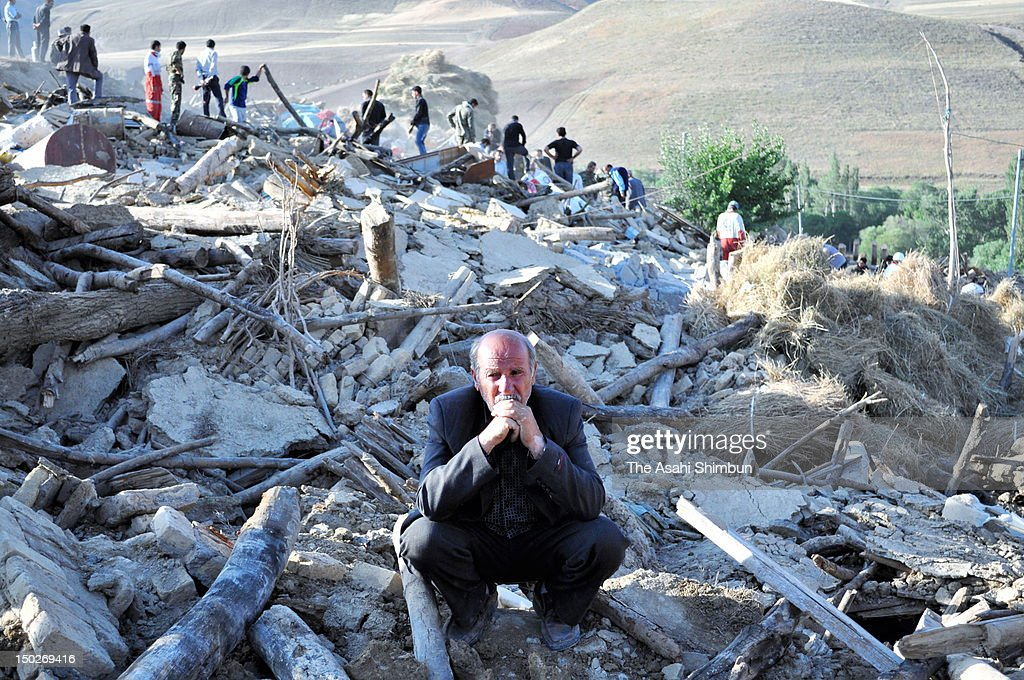 A man sit at the place where his house used to be, on August 12, 2012 in Varzaqan, Iran. The two earthquake, within 11 minutes, jolted northwestern Iran on August 11, killed at least 300 people.