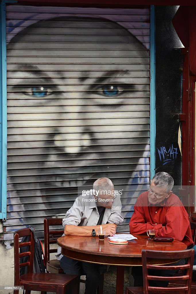 Man sit outside as graffiti lines Denoyez street in the Belleville quarter on October 18, 2014 in Paris, France. Denoyez Street is dedicated to street art and is one of a few legalized laneways for graffiti in the city. The collective of Desnoyez street artists argues that the street has become an example of a mixed community living in creating a harmony and balance that is now threatened by the mayor's proposal to demolish a stretch of the street.