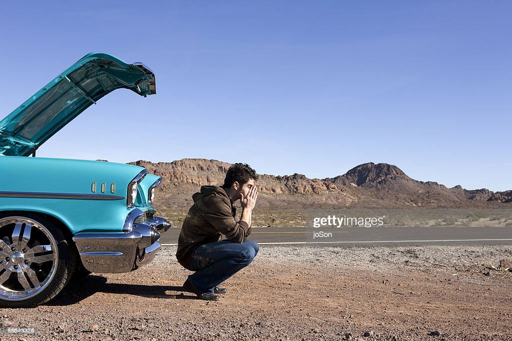 Man siting in front of broken down vintage car