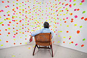 man siting in front of post it notes on the wall