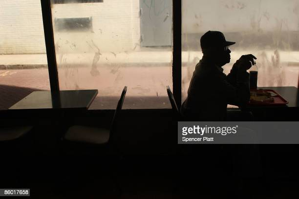 A man sits alone in a fast food restaurant April 17 2009 in Newark New Jersey Newark New Jersey's largest city is struggling to hold onto economic...