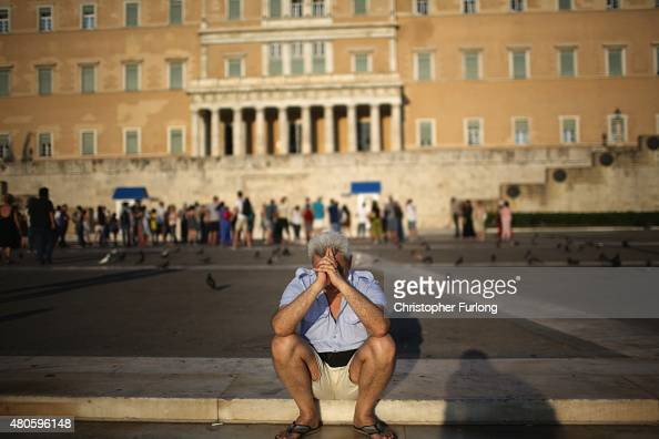 A man sits alone with his thoughts as protesters gather outside the Greek parliament to demonstrate against austerity after an agreement for a third...
