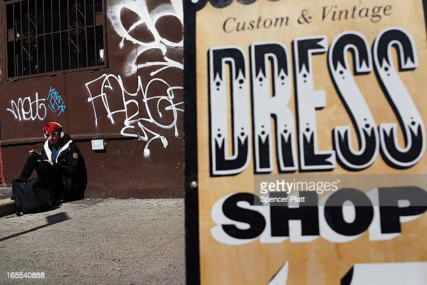 A man sits along a street in the rapidly developing neighborhood of Williamsburg on April 4 2013 in the Brooklyn borough of New York City Two Trees...