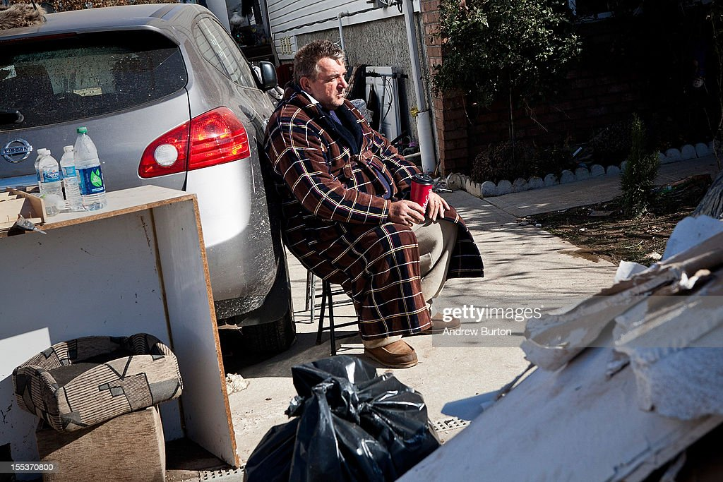 A man sits amidst the aftermath of Superstorn Sandy in the Midland Beach neighborhood of Staten Island on November 3, 2012 in New York City. As clean up efforts from Superstorm Sandy continue, colder weather and another storm predicted for next week are beginning to make some worried.